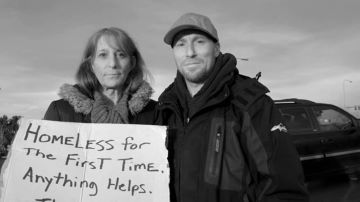 "Two people outdoors holding a sign that reads ""Homeless for the first time, anything helps"""