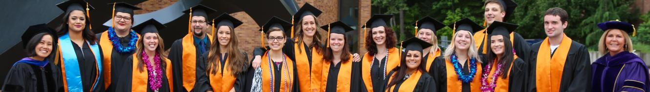 RN-BSN students in their gowns at graduation gathered for a group photo